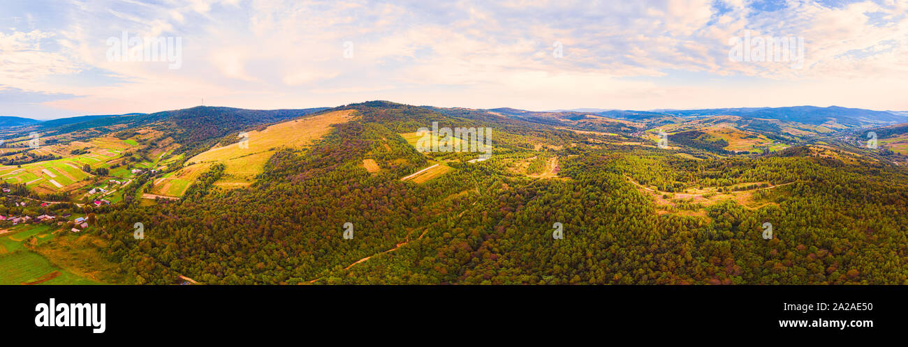 180 degrees panoramic landscape of countryside, aerial drone view of nature in Carpathians. Sunset time, end of summer. Stock Photo