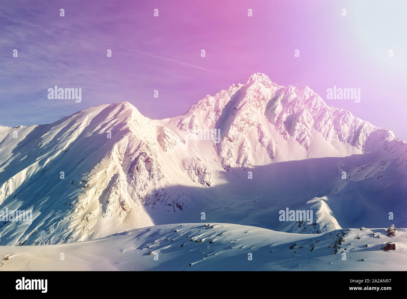 Dramatic scenic pink to purple sunrise in austrian alpine mountain peaks covered with snow layer in winter . Idyllic clear sky on background. Natural Stock Photo