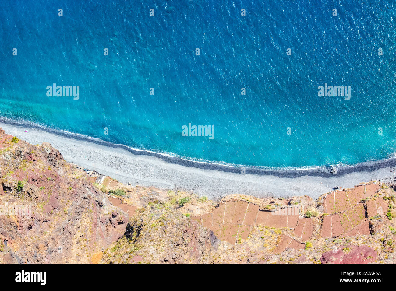 Aerial view of the blue Atlantic ocean, beach and adjacent fields on the southern coast of Madeira Island, Portugal. Aerial landscape, amazing nature. Summer vibes. Stock Photo