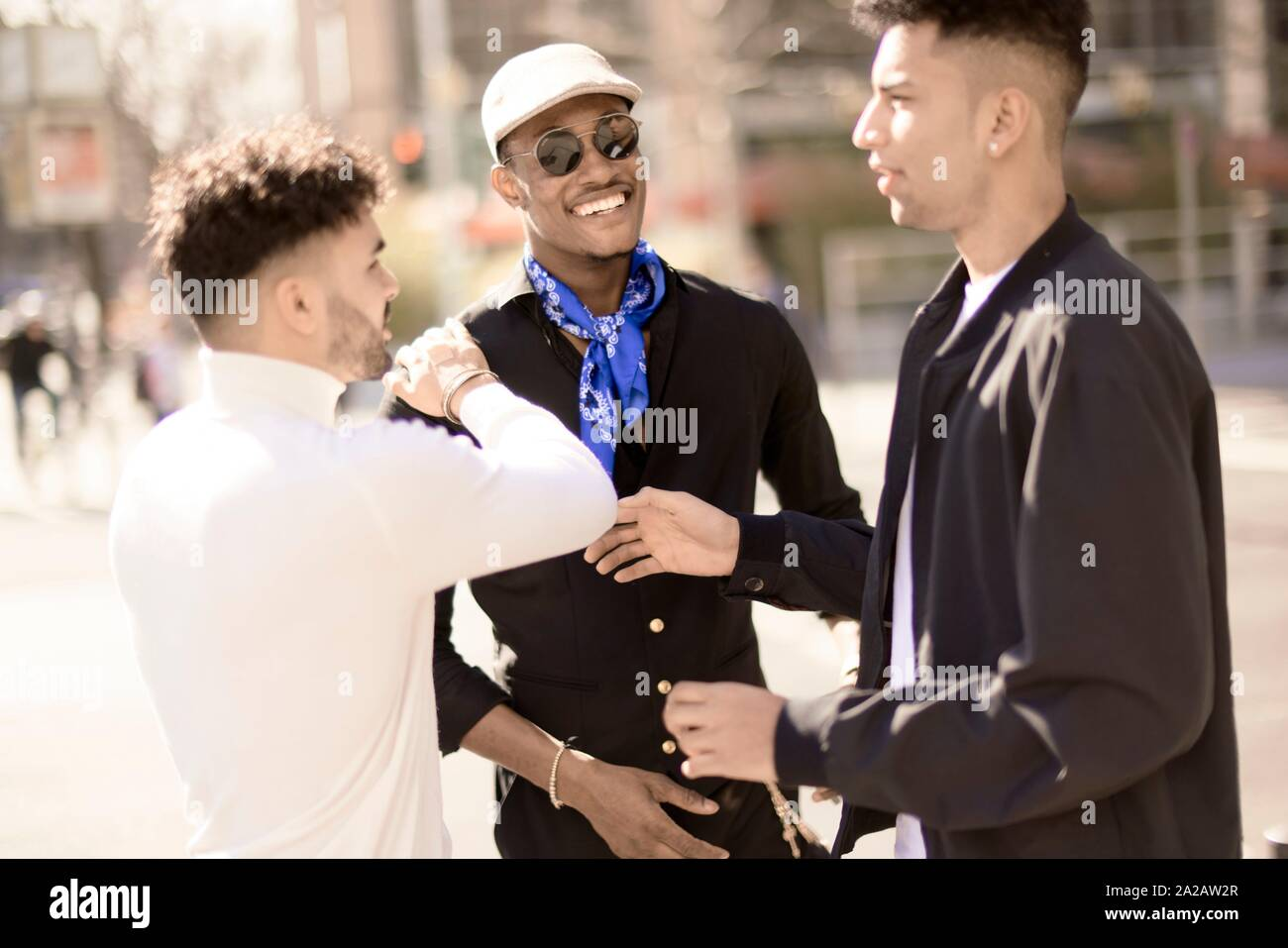 three male friends discussing on street in city Frankfurt, Germany Stock Photo