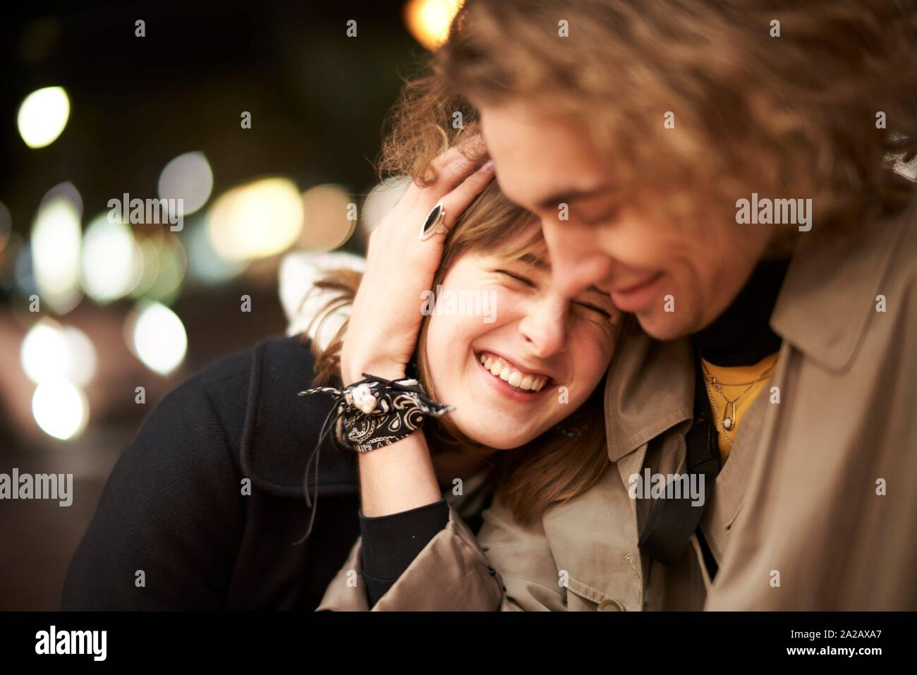 woman laughing in arms of man at night in city Berlin, Germany. Stock Photo