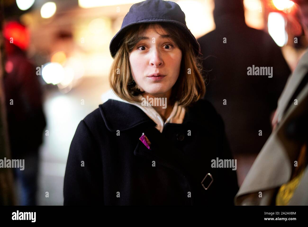 woman making big eyes at night on street Stock Photo