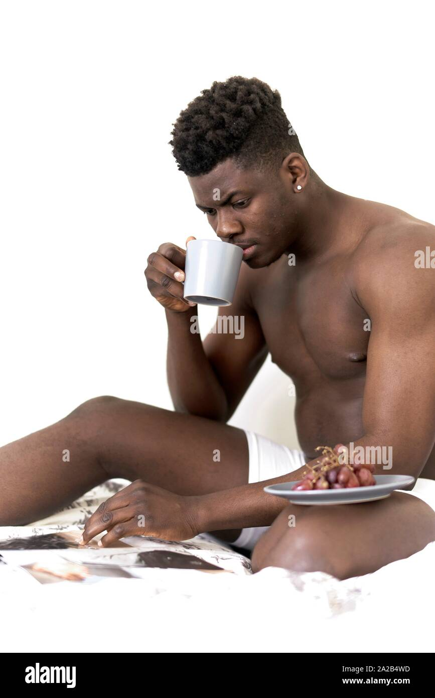 man with breakfast, grapes and coffee, reading newspaper in bed, getting up, in Munich, Germany Stock Photo