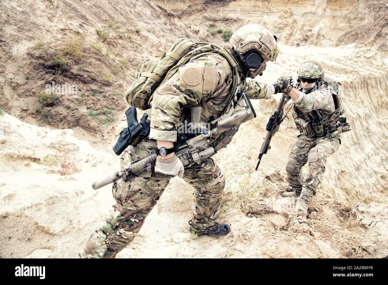US ranger, modern infantryman, special reconnaissance team member or military scout in ammunition, armed with service rifle helping brother in arms Stock Photo
