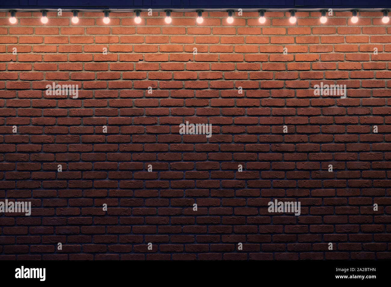An orange brick wall with small light bulbs. Gradient stone background with low light and copy space. Place for advert. Stock Photo