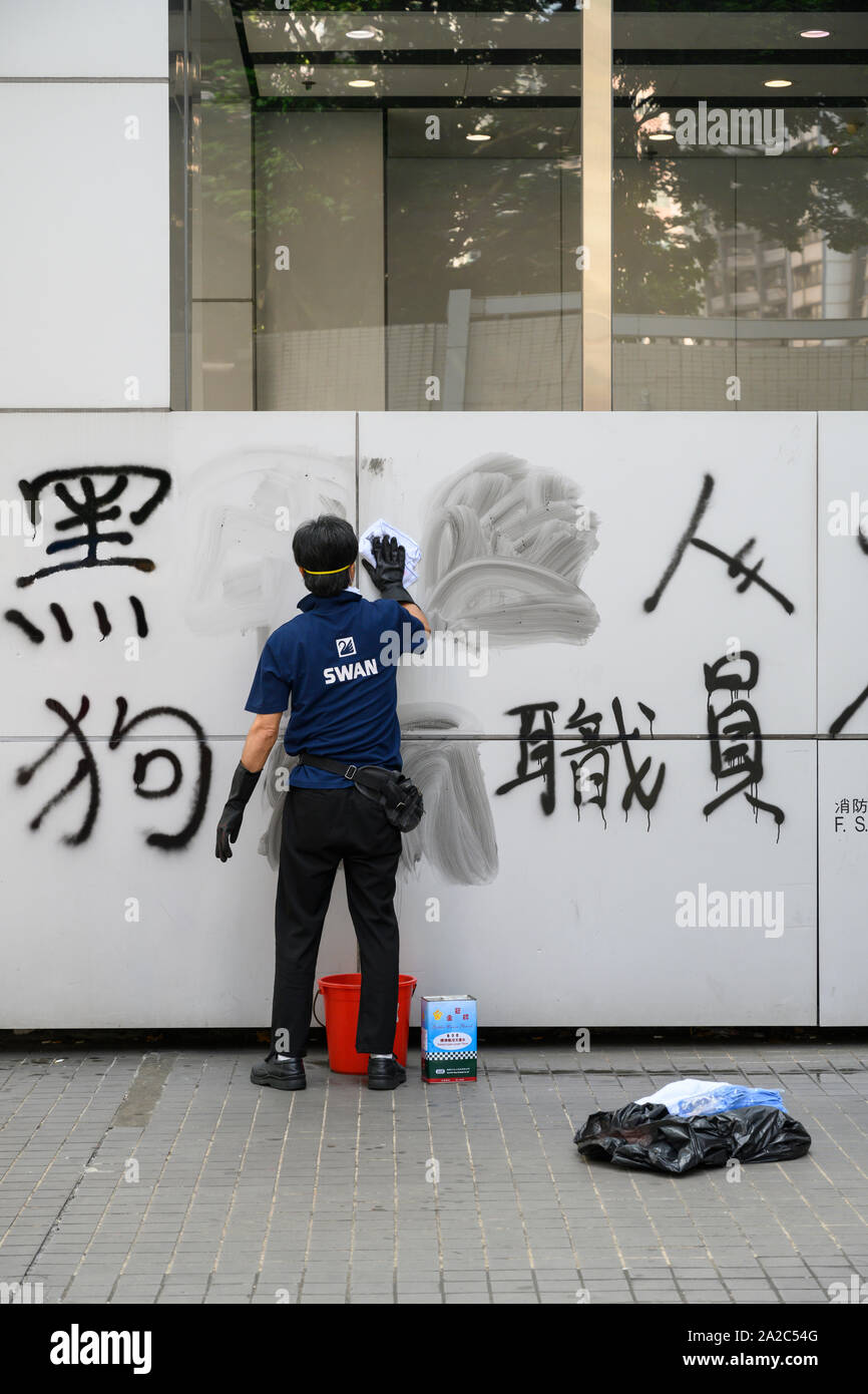 October 2 2019.  Hong Kong resumes business the morning after violent protests on October 1 2019. Workers clean graffiti off of walls and billboards. Stock Photo