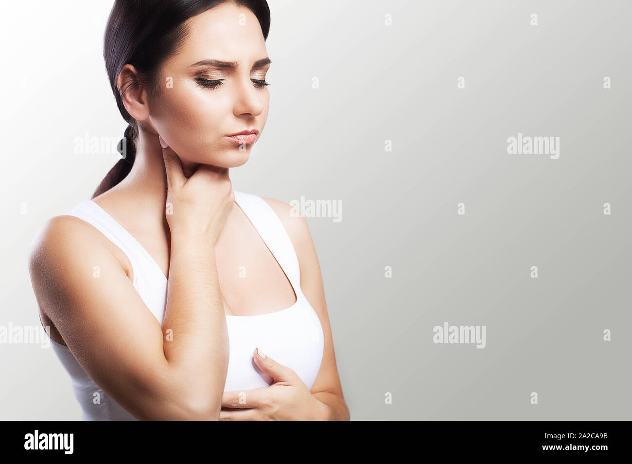 Sore throat. Sick woman, flu Young beautiful woman with sore throat. Feeling painful in the throat. The concept of health. On a gray background. Stock Photo