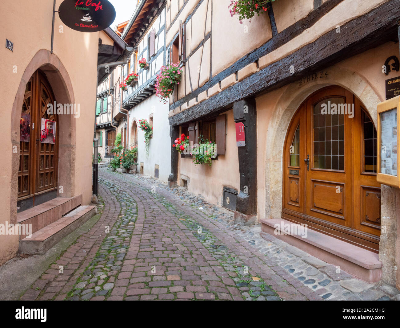 Half timbered buildings in the centre of Eguisheim Alsace France a pretty medieval town in the heart of the Alsace wine region and popular travel dest Stock Photo