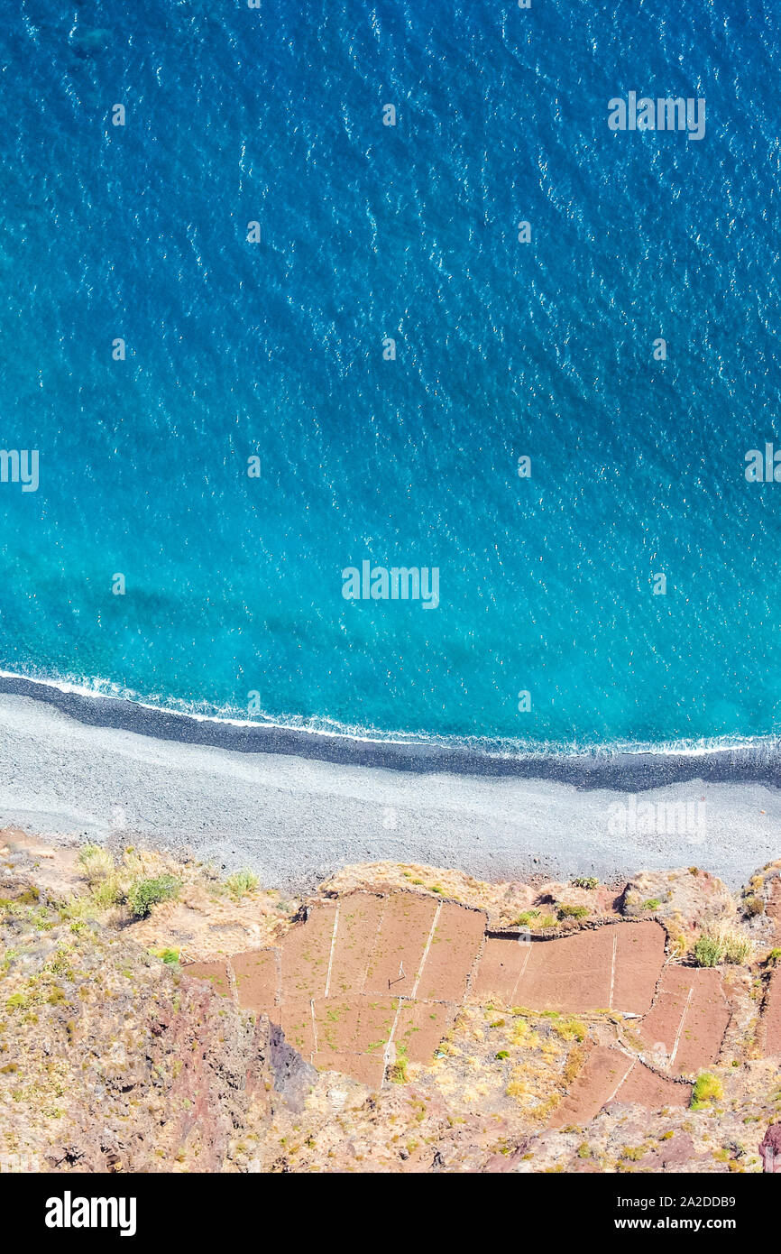 Aerial landscape by the blue Atlantic ocean. Stone beach and adjacent fields on the southern coast of Madeira Island, Portugal. Aerial view, amazing nature. Summer vibes on a vertical photo. Stock Photo
