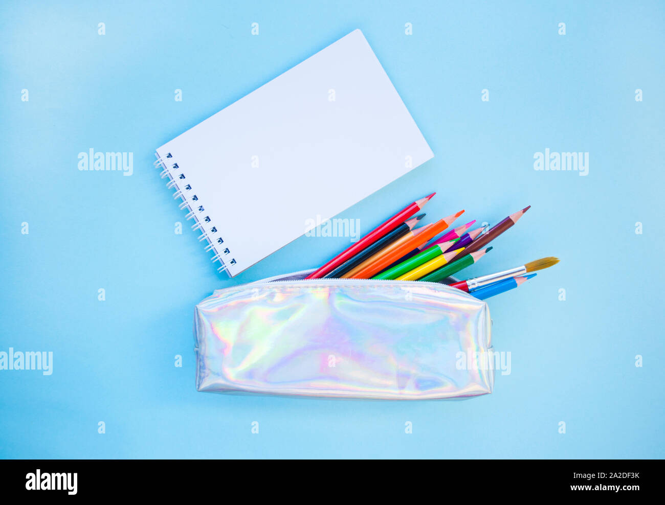 Colorful pencils, watercolors, holographic pencil box on blue background with copyspace. Flat lay style. Back to school concept. Stock Photo