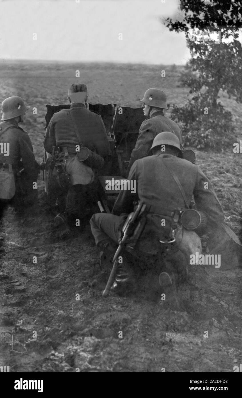Soldaten des Infanterieregiments 9 üben auf einem Truppenübungsplatz mit dem 7,5 cm leichten Infanteriegeschütz 18, Deutschland 1930er Jahre. Infantry soldiers on a military training ground exercising with an infantry support gun, Germany 1930s. Stock Photo