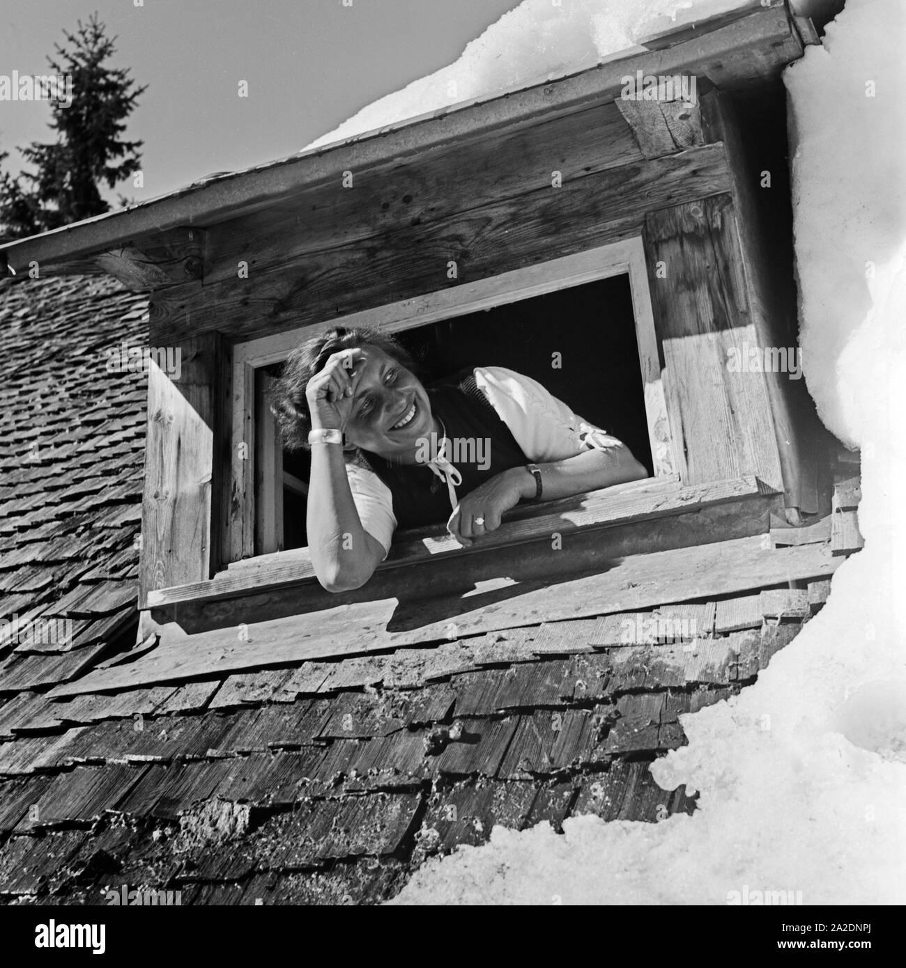 Eine junge Frau schaut aus einem verschneiten Dachfenster, Deutschland 1930er Jahre. A young woman at a snowed in roof window, Germany 1930s. Stock Photo