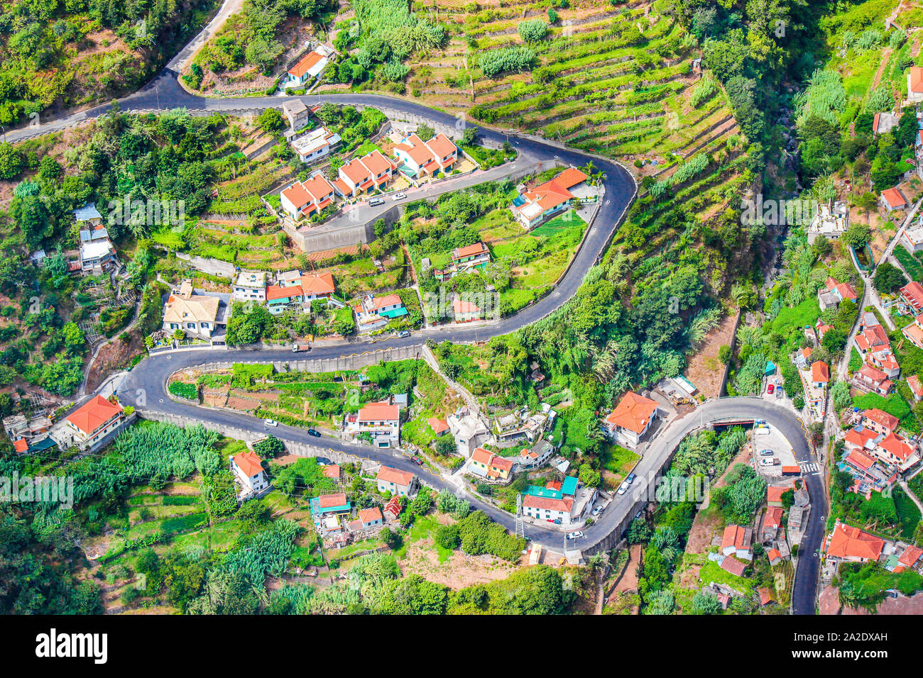 Aerial view of a village Curral das Freiras, Madeira Island, Portugal. Rural houses, green terraced fields, and scenic serpentine road photographed from above. Aerial landscape. Travel destination. Stock Photo
