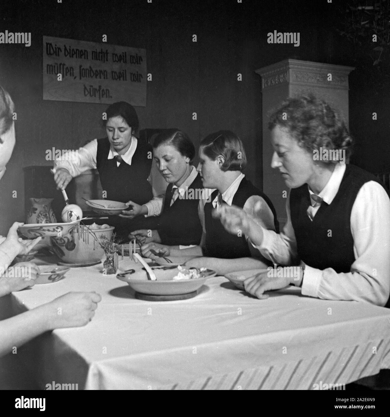 Gemeinsames Essen beim weiblichen Arbeitsdienst in Molkenberg bei Fürstenwalde, Deutschland 1930er Jahre. Women come together and having lunch at the female workforce group of Molkenberg, Germany 1930s. Stock Photo