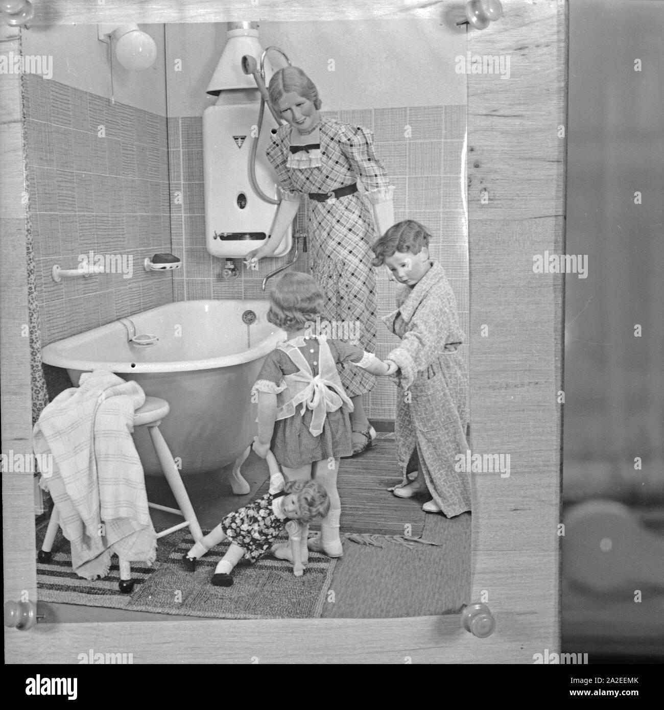 Foto eines Displayaufbaus einer Badezimmer Szenerie mit Käthe Kruse Schaufensterpuppen, Bad Kösen, Deutschland 1930er Jahre. Foto of a bathroom display with Kaethe Kruse display dummies, Germany 1930s. Stock Photo