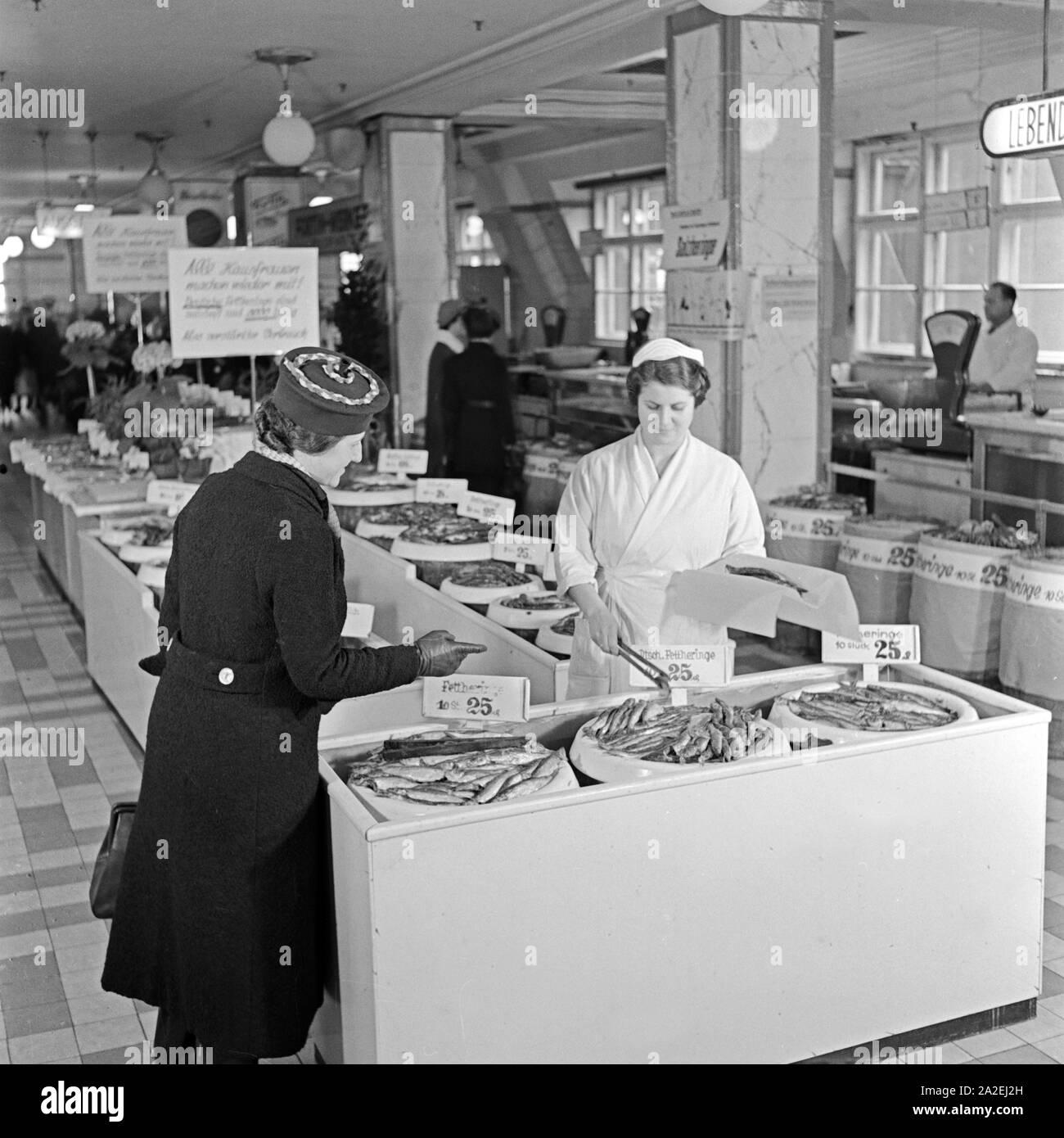 Die Fischabteilung in einem großen Lebensmittelgeschäft bietet Salzheringe an, eine Kundin wird an der Frischetheke bedient, Deutschland 1930er Jahre. The fish department at a grocery offering salted herrings, a woman is served by a shop assistant, Germany 1930s. Stock Photo