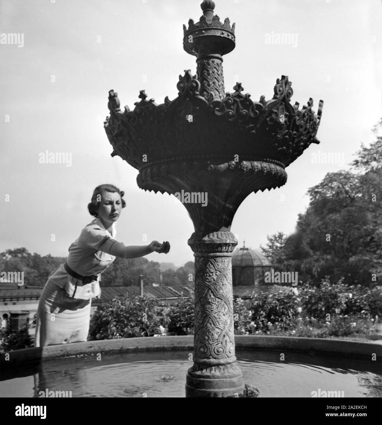 Frau am Springrbunnen vor der Maurischen Festhalle bei der Wilhelma in Stuttgart, Deutschland 1930er Jahre. Woman at a fountain near the Moorish hall at the Wilhelma gardens at Stuttgart, Germany 1930s. Stock Photo