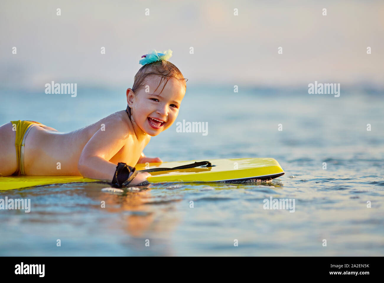 golden waves of wonderful sea splashing near adorable girl in swimsuit carrying yellow surfboard Stock Photo