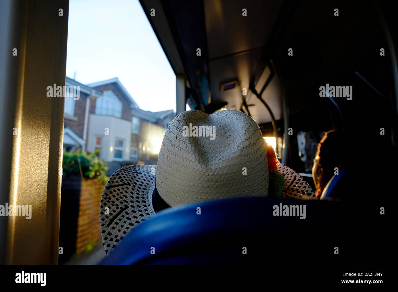 Bus passenger's view out of the window from behind a passenger wearing a stetson style straw hat Stock Photo