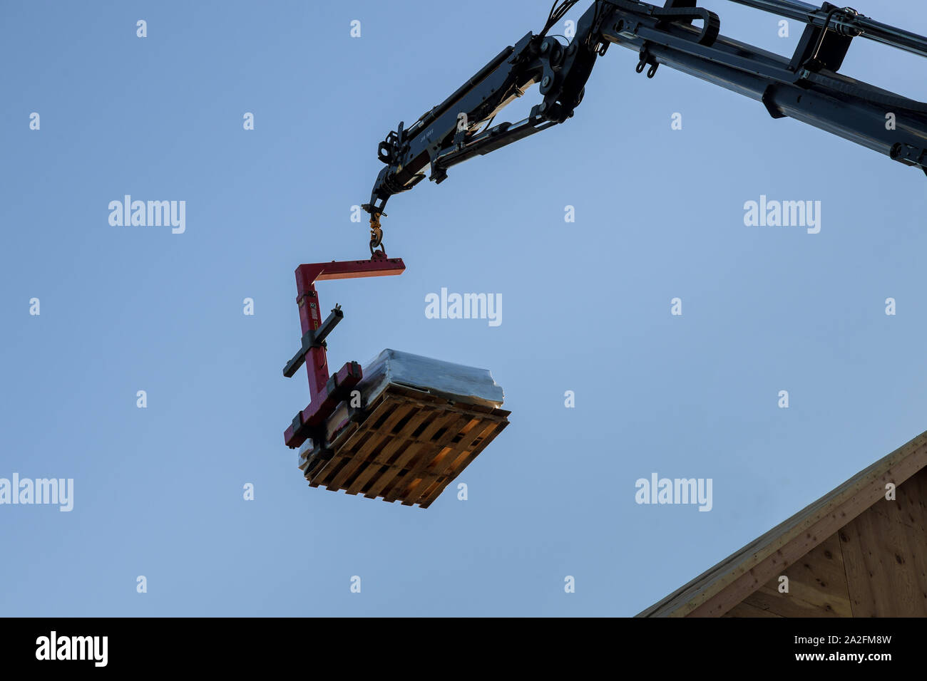 Construction building industry details in progress boom truck forklift crane roof into plate on new home Stock Photo