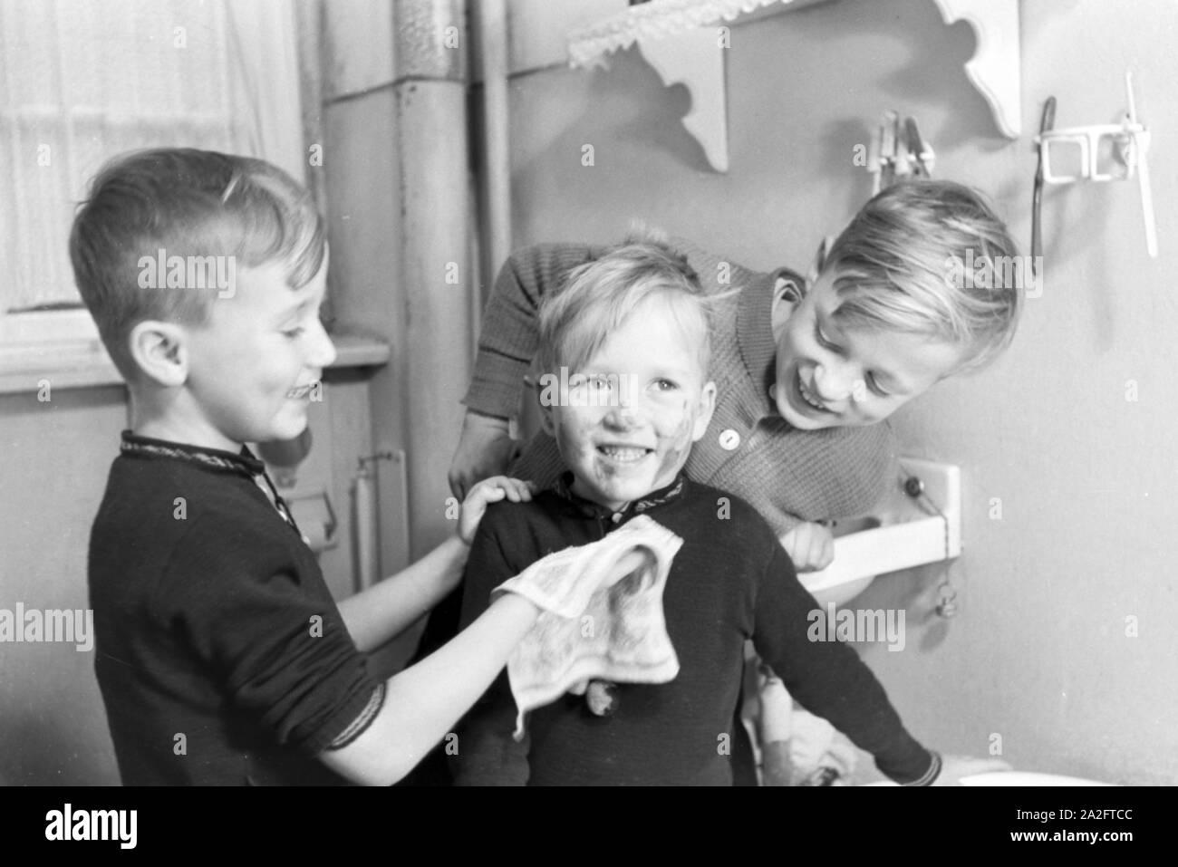 Die Söhne einer kinderreichen Familie waschen sich im Badezimmer, Deutsches Reich 1930er Jahre. Sons of a extended family having a wash in the bathroom, Germany 1930s. Stock Photo
