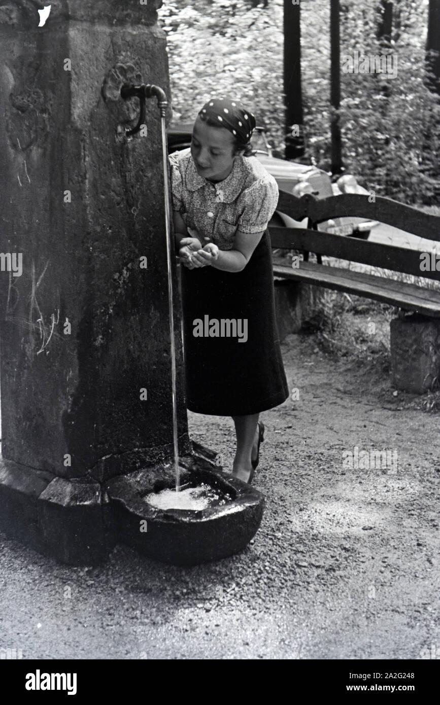 Eine junge Frau probiert das Trinkwasser des Eberbrunnens auf einem Wanderpfad bei Baden-Baden im Nordschwarzwald, Deutschland 1930er Jahre. A young w Stock Photo