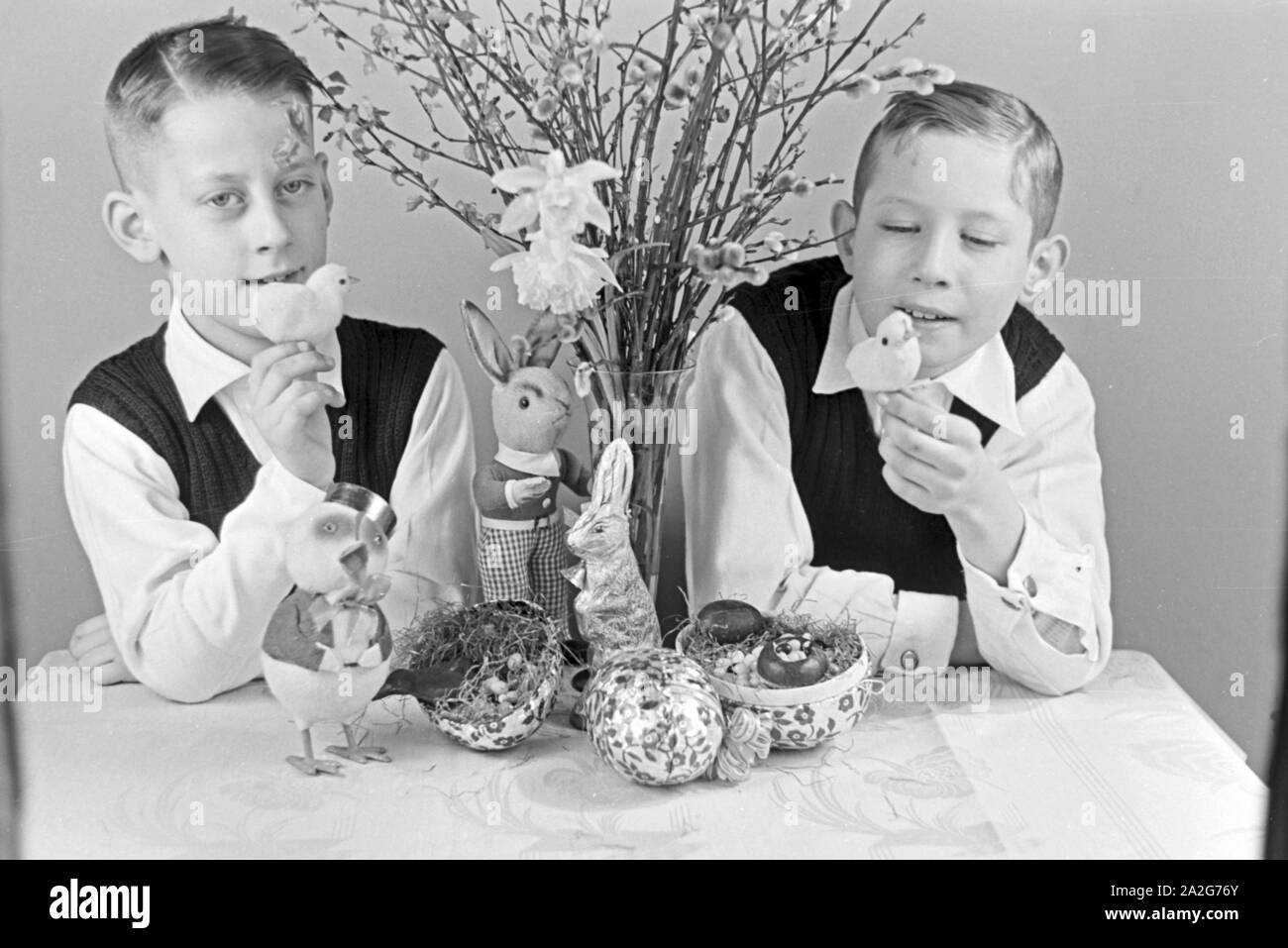 Zwei Jungen mit Ostedekoration, Deutschland 1930er Jahre. Two boys at a table with easter decoration, Germany 1930s. Stock Photo
