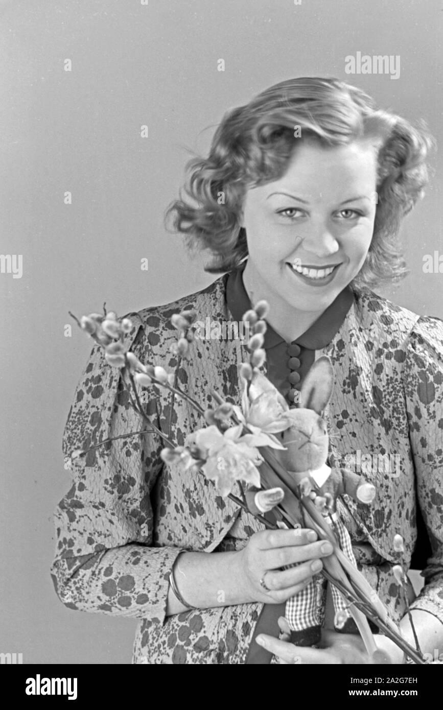 Porträt eines jungen Mädchens, Osterdekoration in den Händen haltend, Deutschland 1930er Jahre. Portrait of a young girl holding some easter decoration in her hands, Germany 1930s. Stock Photo
