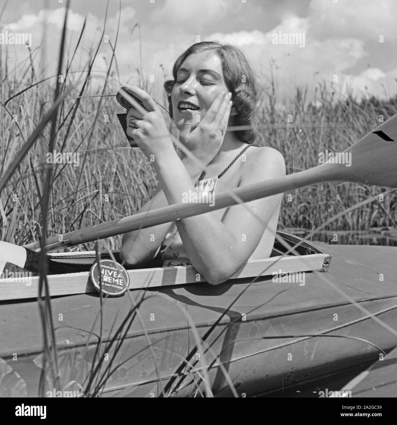 Eine junge Frau cremt sich mit Nivea Creme beim Badeurlaub ein, Deutschland 1930er Jahre. A young woman using sunblocker, Germany 1930s. Stock Photo