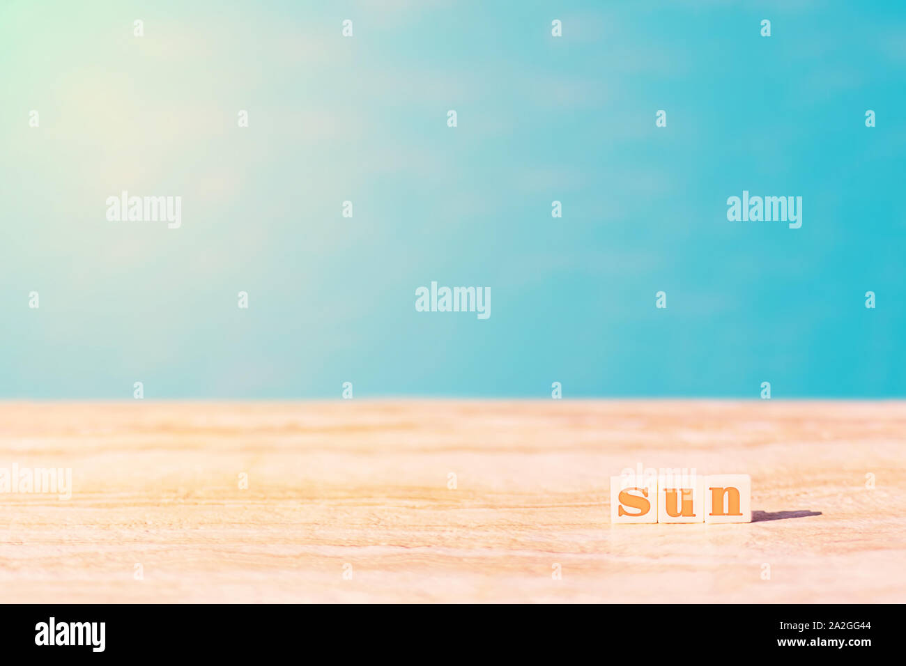 Word sun written by cubes near the pool. Azure water in sunny day used as a background. Sun light and copy space. Summer and vacation concept. Stock Photo
