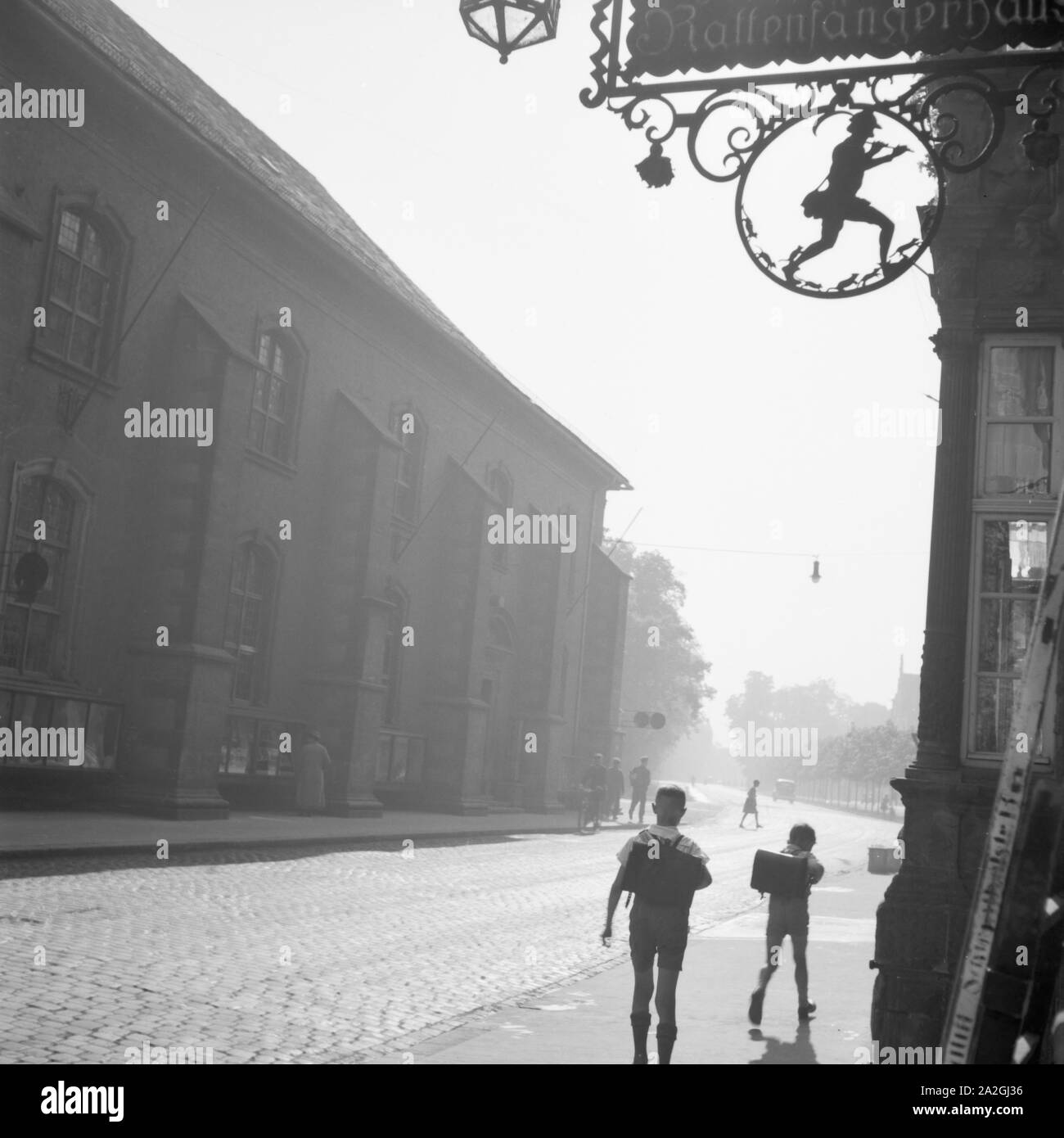 Schulkinder vor einem Haus mit dem Rattenfänger Symbol in Hameln an der Weser, Deutschland 1930er Jahre. School kids in front of a house with the Pied Piper's symbol at the old city of Hameln on river Weser, Germany 1930s. Stock Photo