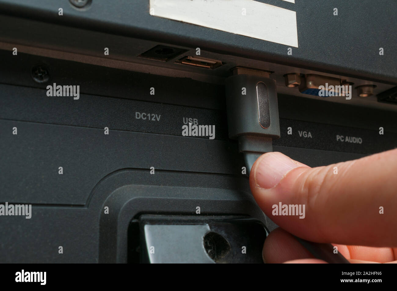 Man plug a hdmi cable in a tv Stock Photo
