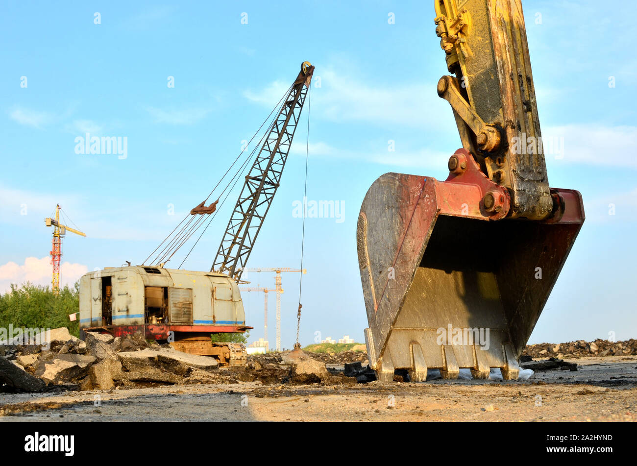 Excavator bucket on the construction site at sunset background and of the blue sky. Land Clearing, grading, pool excavation, utility trenching, utilit Stock Photo