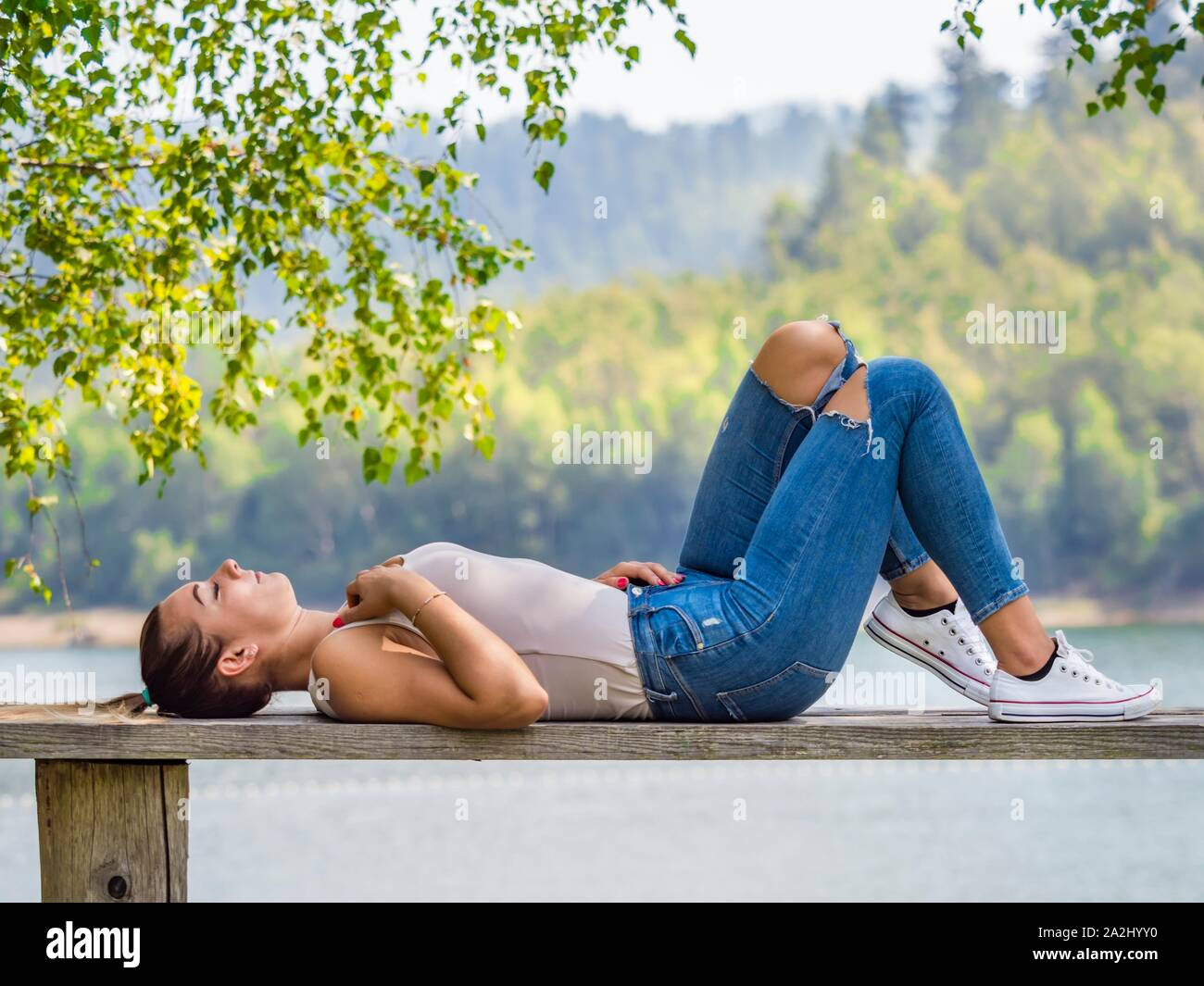 Young woman wearing Blue denim pants denims is resting lying on her back on wooden bench in park near lake country-side countryside in on at near but Stock Photo
