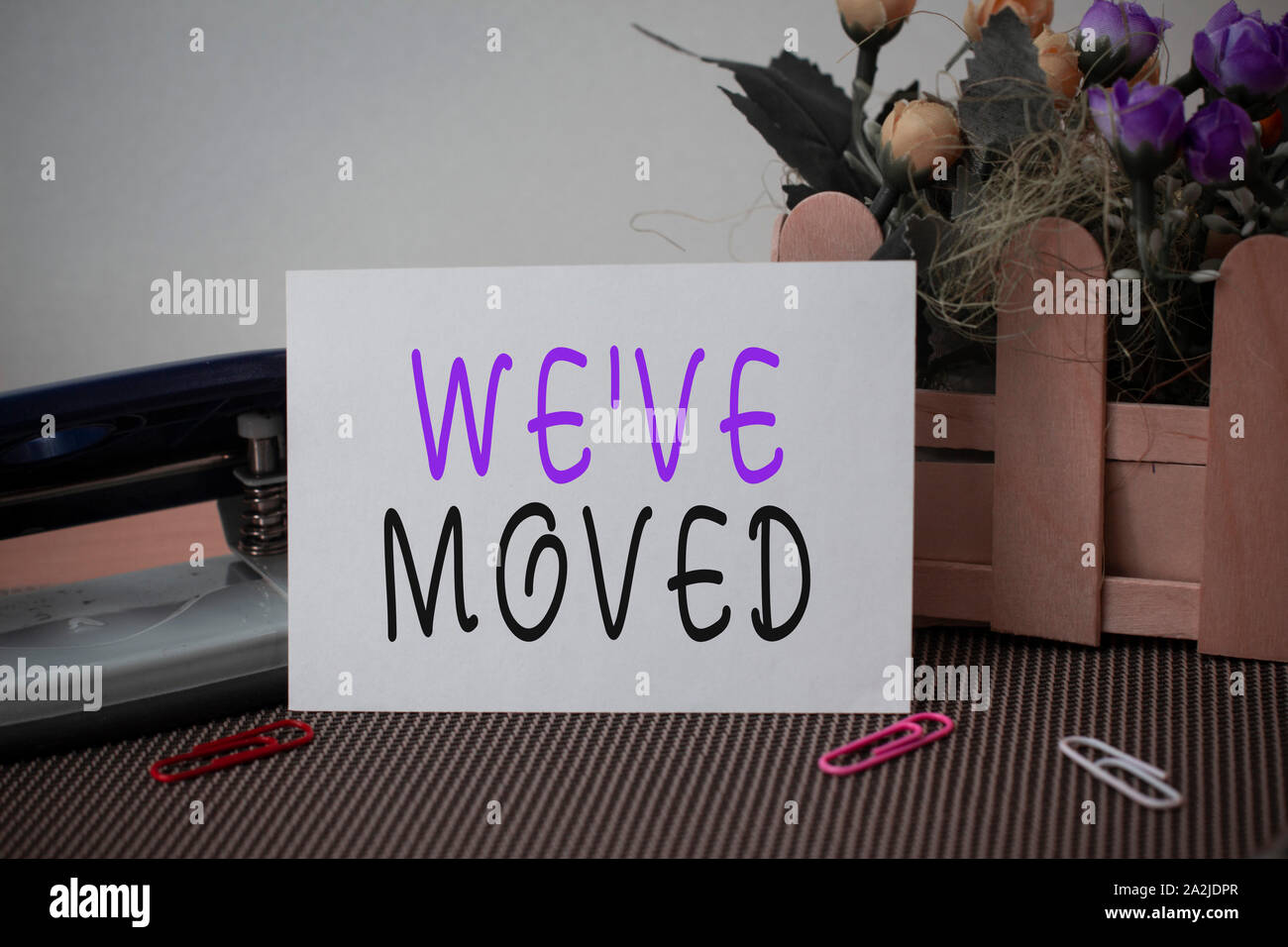 Text sign showing We Ve Moved. Business photo text going to live from place another same or different country Flowers and writing equipments plus plai Stock Photo