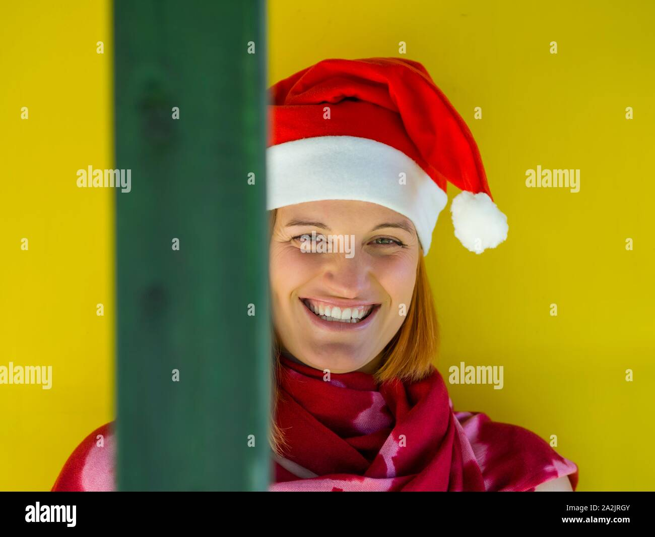 Happy and smiling female Red Santa portrait head and shoulders Yellow background eyeshot looking at camera eye eyes contact Stock Photo