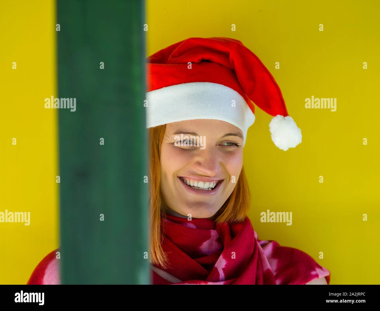 Happy and smiling female Red Santa portrait head and shoulders Yellow background looking away aside Stock Photo