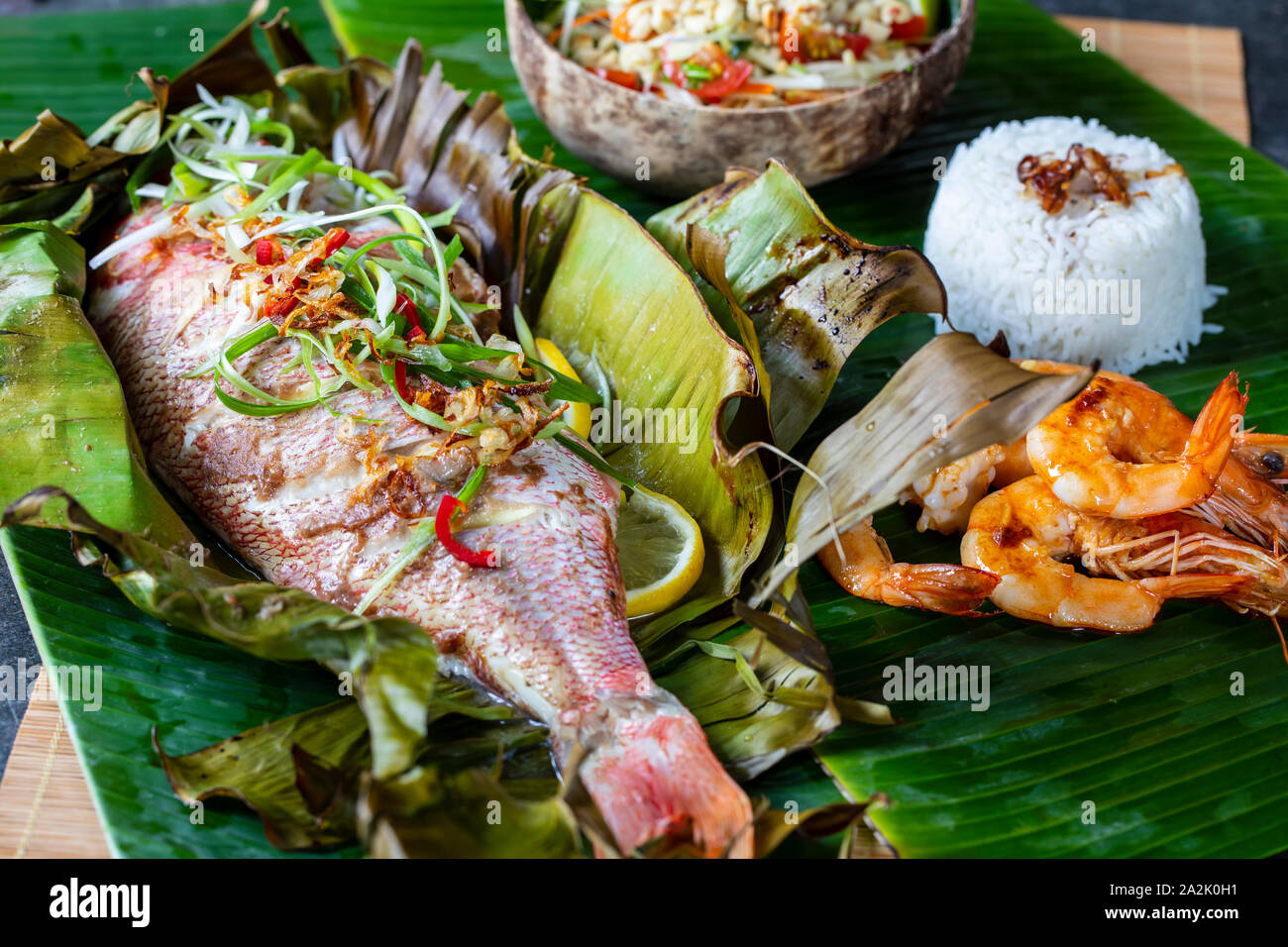 Red snapper baked in banana leaf, papaya salad and rice Stock Photo