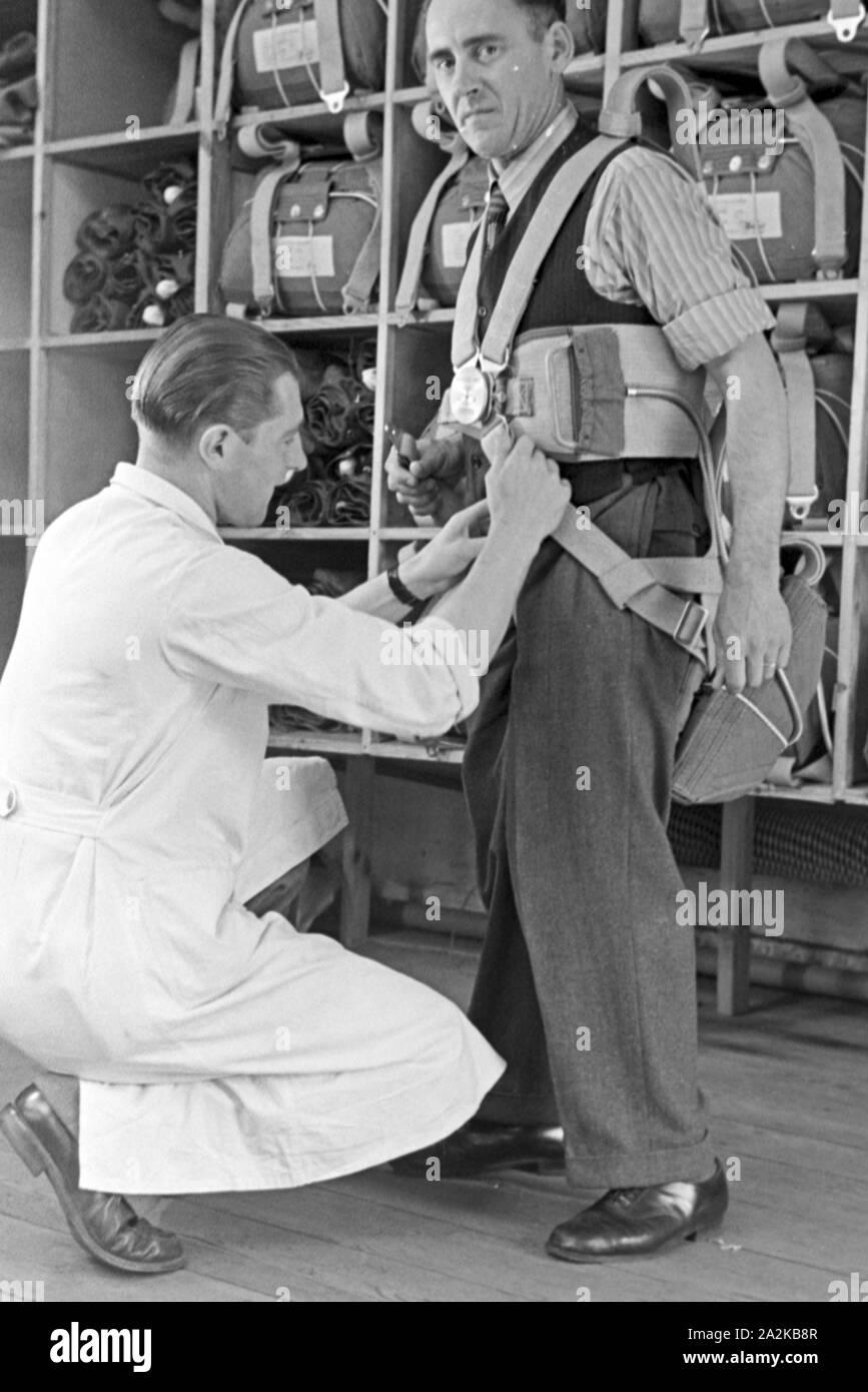 Anpassung des Gurtzeugs eines Fallschirms in einer Fallschirm Näherei, Deutschland 1940er Jahre. Checking the harness of a parachute at a parachute sewing factory, Germany 1940s. Stock Photo