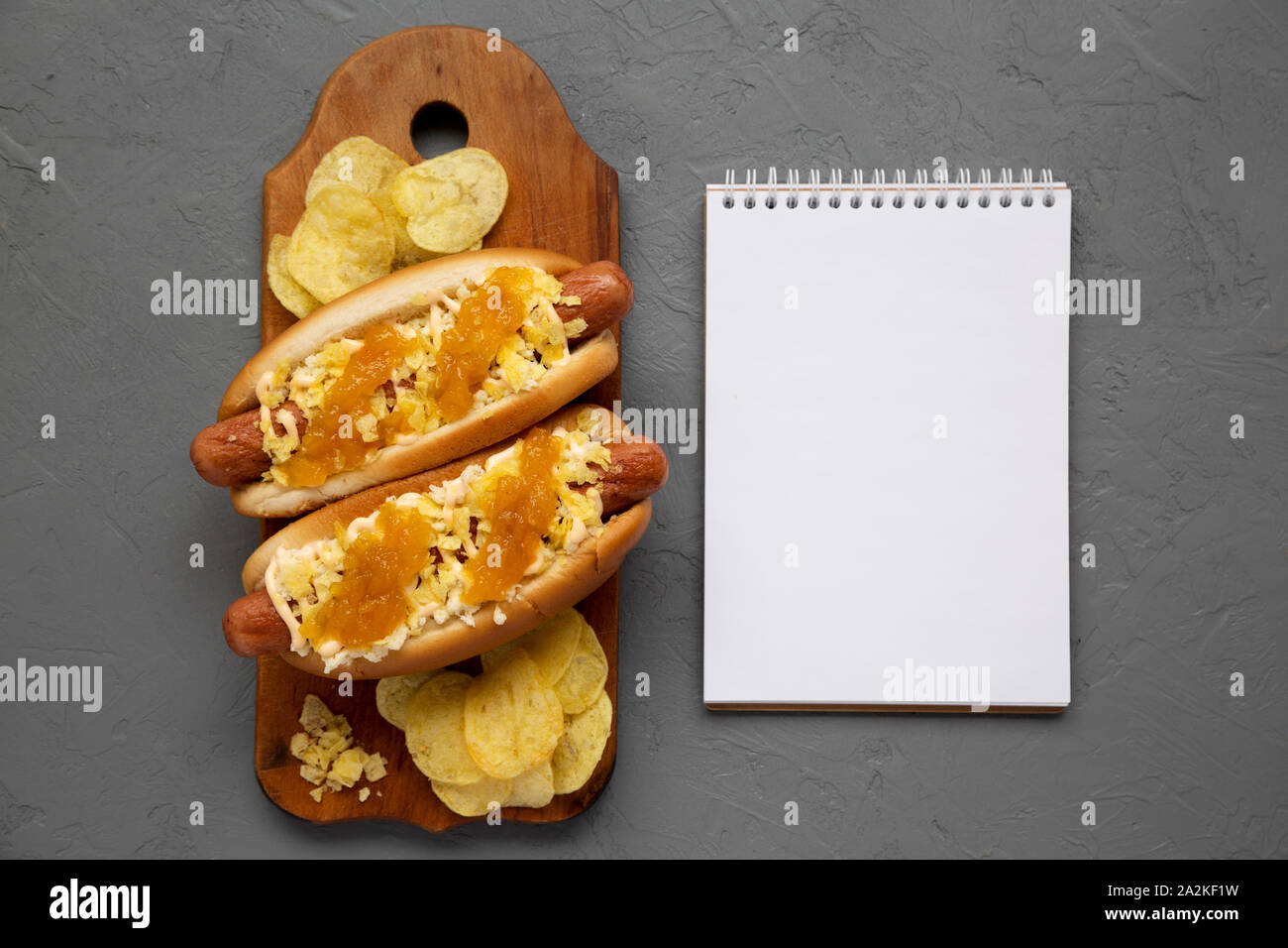 Homemade colombian hot dogs with pineapple sauce, chips and mayo ketchup on a rustic wooden board, blank notepad on a gray background. Flat lay, from Stock Photo