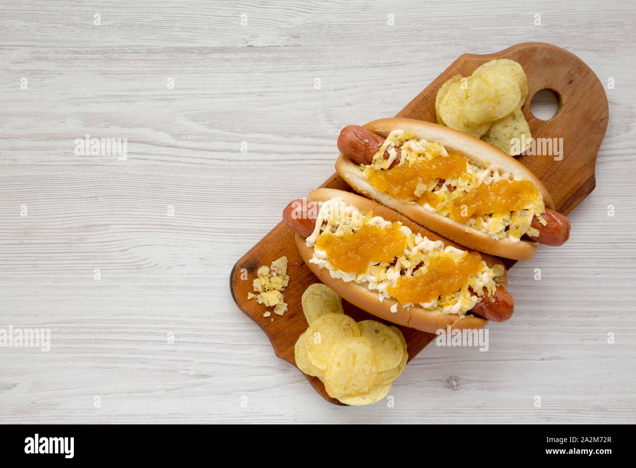 Homemade colombian hot dogs with pineapple sauce, chips and mayo ketchup on a rustic wooden board on a white wooden background, top view. Overhead, fl Stock Photo