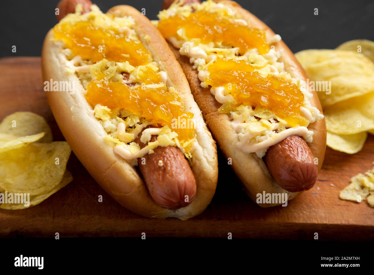 Homemade colombian hot dogs with pineapple sauce, chips and mayo ketchup on a rustic wooden board on a black background, side view. Close-up. Stock Photo