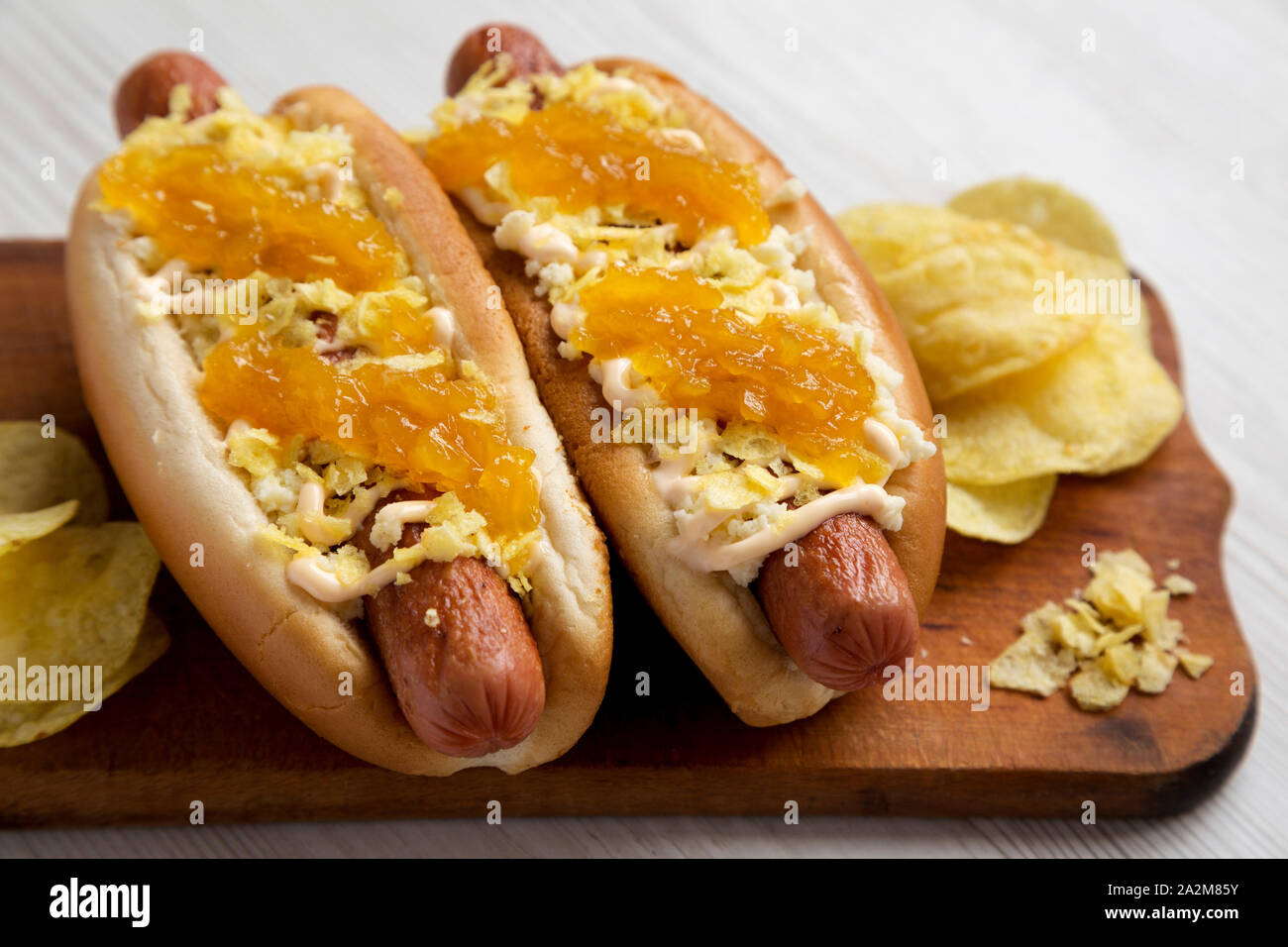 Homemade colombian hot dogs with pineapple sauce, chips and mayo ketchup on a rustic wooden board on a white wooden surface, side view. Closeup. Stock Photo