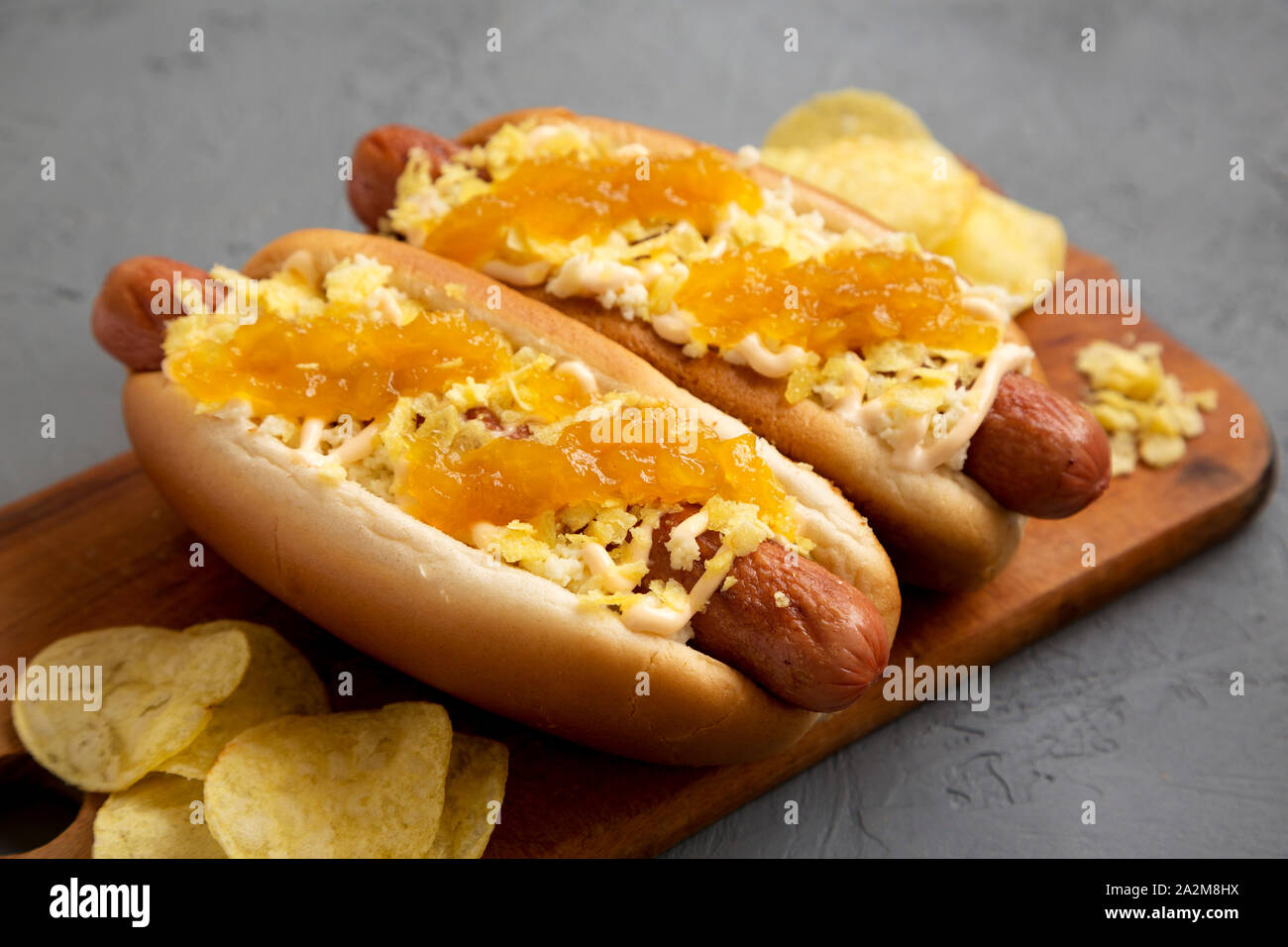 Homemade colombian hot dogs with pineapple sauce, chips and mayo ketchup on a rustic wooden board on a gray background, side view. Close-up. Stock Photo