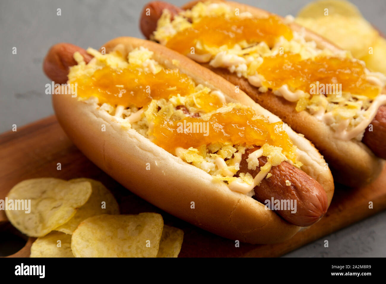 Homemade colombian hot dogs with pineapple sauce, chips and mayo ketchup on a rustic wooden board on a gray surface. Flat lay, from above, top view. C Stock Photo