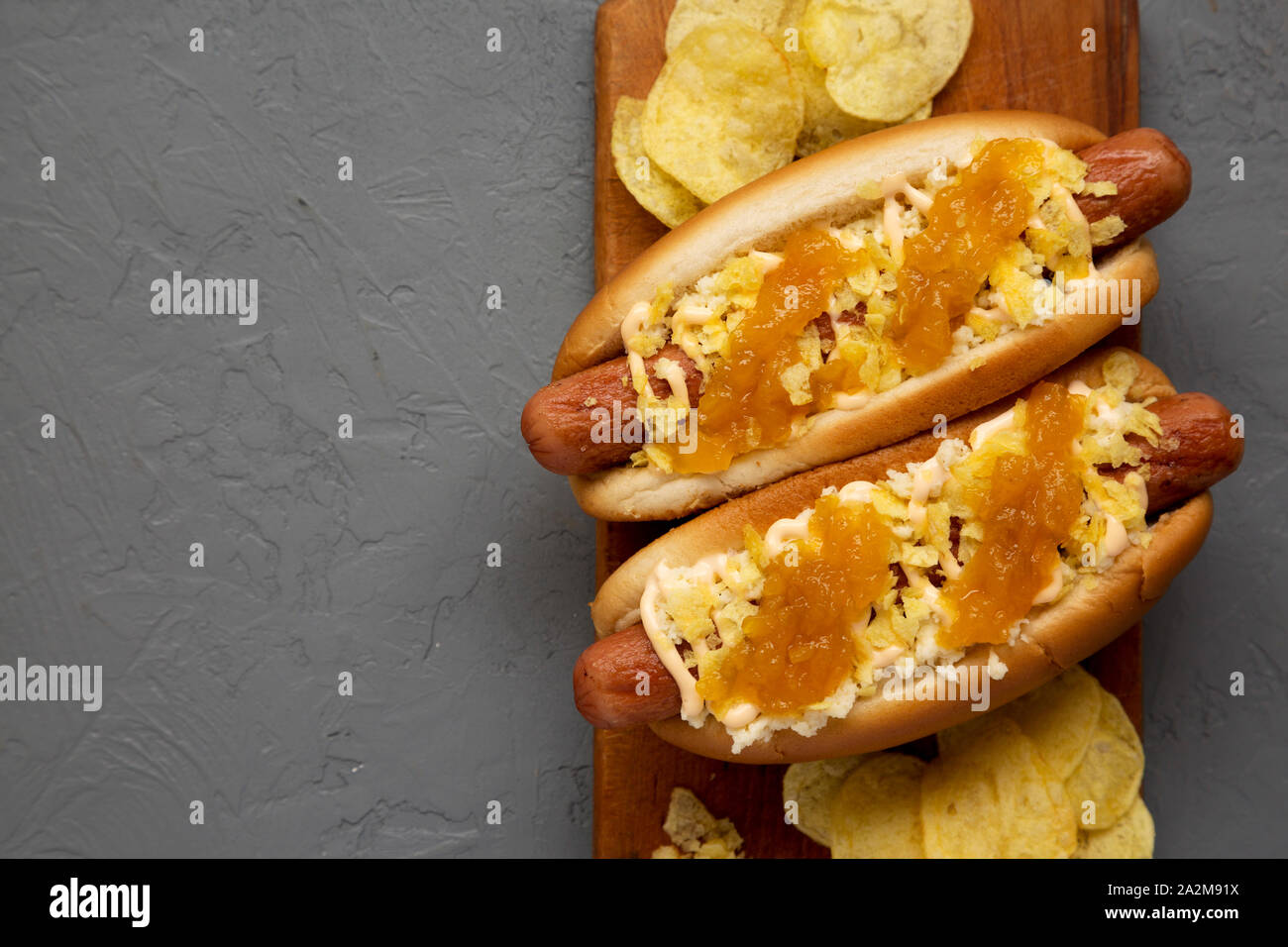 Homemade colombian hot dogs with pineapple sauce, chips and mayo ketchup on a rustic wooden board on a concrete background. Flat lay, from above, top Stock Photo