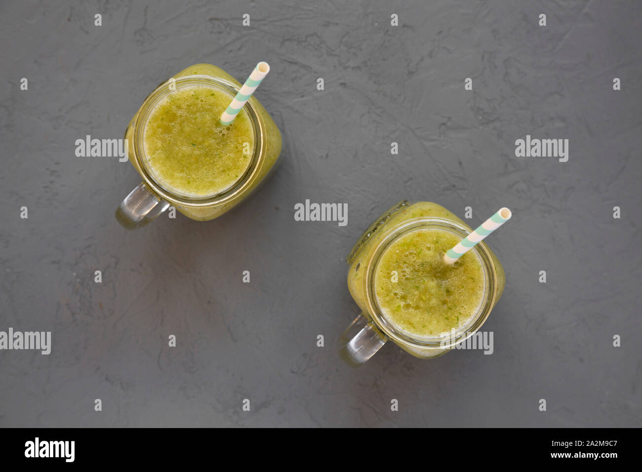 Homemade green cucumber apple smoothie in glass jars on a gray background, top view. Flat lay, overhead, from above. Stock Photo