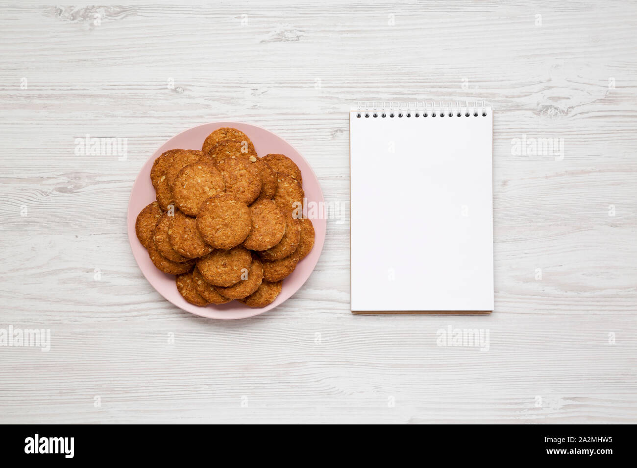 Cereal cookies on a pink plate, blank notepad on a white wooden surface, overhead view. Flat lay, top view, from above. Stock Photo