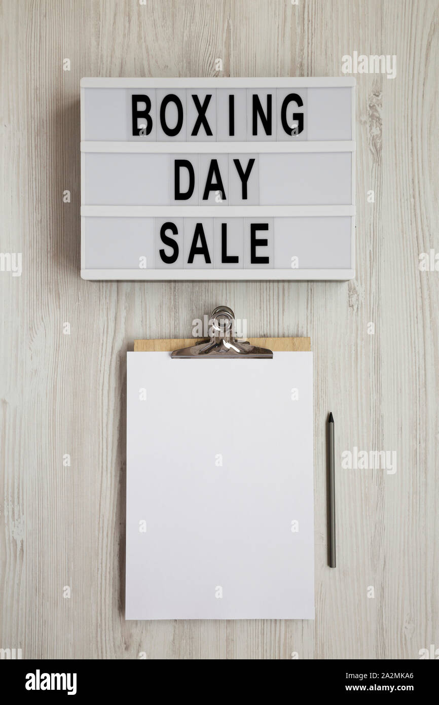 'Boxing day sale' words on a lightbox, clipboard with blank sheet of paper on a white wooden background, top view. Overhead, from above, flat lay. Cop Stock Photo