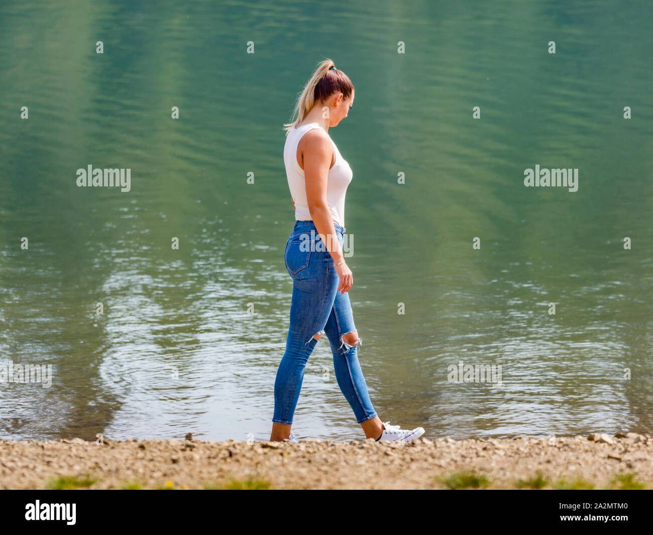 Attractive young woman wearing Blue denim pants denims is walking along lake coastline looking away Stock Photo